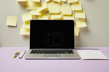Photo for Laptop with blank screen near yellow sticky notes and stationery on grey and purple - Royalty Free Image