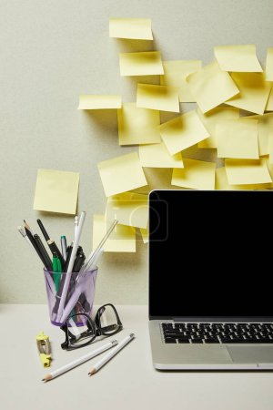Photo for Laptop with blank screen near empty sticky notes and pen holder with stationery on grey and white - Royalty Free Image