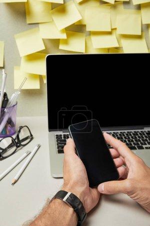 Photo pour Crochet vu d'un homme tenant un smartphone avec écran vierge près d'un ordinateur portable, lunettes et papeterie en gris et blanc - image libre de droit