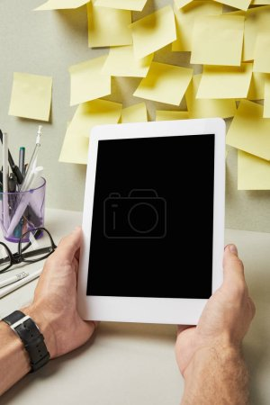 Photo for Cropped view of man holding digital tablet with blank screen near stationery on grey and white - Royalty Free Image
