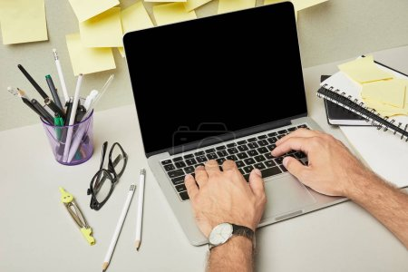 Photo for Cropped view of man using laptop with blank screen near stationery and sticky notes on grey and white - Royalty Free Image
