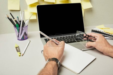 Photo for Cropped view of man holding glasses while writing on notebook near laptop with blank screen and stationery on grey and white - Royalty Free Image