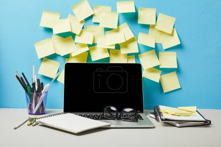 Photo for Laptop with blank screen near sticky notes, notebooks and stationery on blue and white - Royalty Free Image