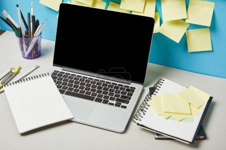Photo pour Ordinateur portable avec écran vierge près des notes collantes papeterie et cahiers en bleu et blanc - image libre de droit