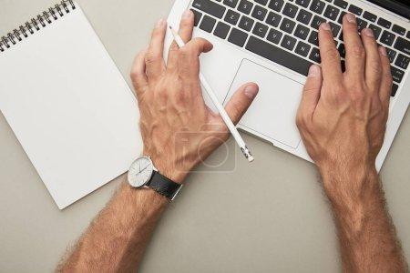 Photo pour Vue recadrée de l'homme tapant sur un ordinateur portable tout en tenant un crayon près d'un ordinateur portable isolé sur gris - image libre de droit