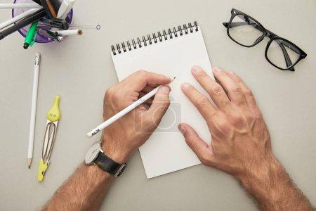 Photo pour Vue recadrée de l'homme écrivant dans un cahier près de lunettes et de papeterie isolé sur gris - image libre de droit