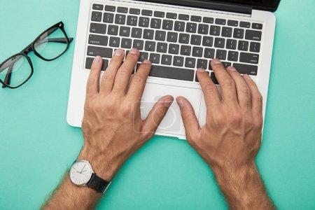 Photo pour Vue de dessus de l'homme tapant sur ordinateur portable près de lunettes isolées sur turquoise - image libre de droit