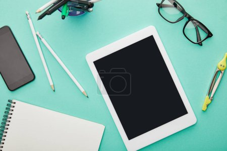 Photo for Top view of gadgets with blank screens near glasses, stationery and notebook isolated on turquoise - Royalty Free Image
