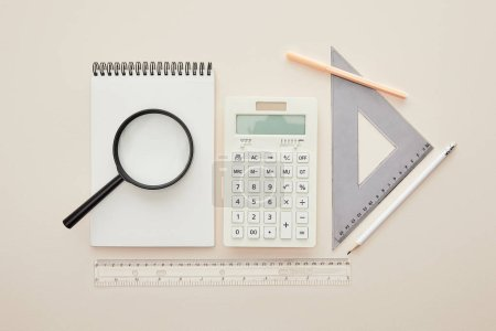 Photo for Top view of magnifier on notebook near stationery isolated on beige - Royalty Free Image
