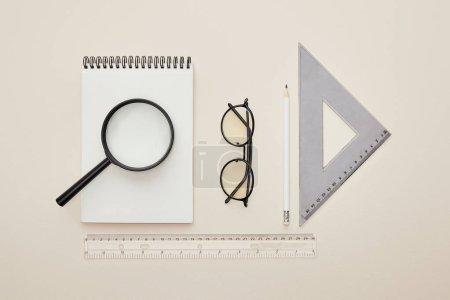 Photo pour Vue du haut de la loupe sur un cahier près des lunettes et des règles isolées sur beige - image libre de droit