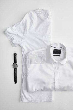Photo pour Vue du dessus de plié en demi-t-shirt près de chemise à carreaux et montres sur fond blanc - image libre de droit