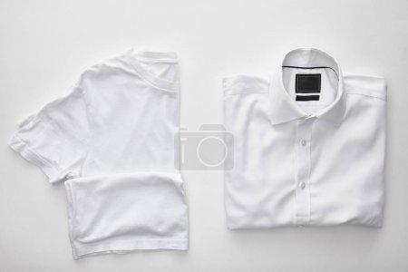 Photo pour Vue du haut du t-shirt vierge près de chemise à carreaux sur fond blanc - image libre de droit