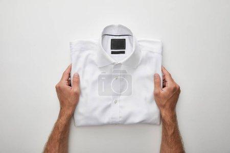 Photo pour Vue recadrée de l'homme tenant chemise pliée sur fond blanc - image libre de droit