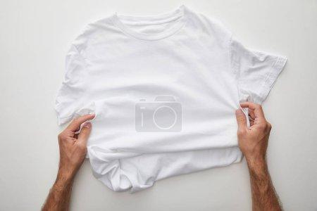 Photo pour Vue recadrée de l'homme tenant t-shirt uni sur fond blanc - image libre de droit