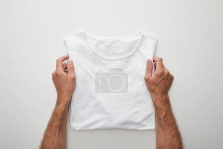 Photo pour Vue recadrée de l'homme tenant un t-shirt uni plié sur fond blanc - image libre de droit