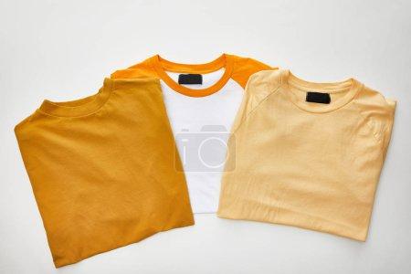 Photo pour Vue de dessus de t-shirts pliés beige, ocre et orange sur fond blanc - image libre de droit