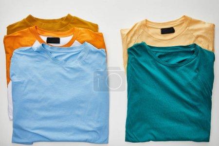 Photo pour Vue supérieure de beige, orange, bleu, turquoise et ocre t-shirts sur fond blanc - image libre de droit