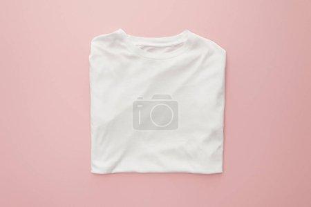 Photo pour Vue du haut du t-shirt blanc plié vierge sur fond rose - image libre de droit