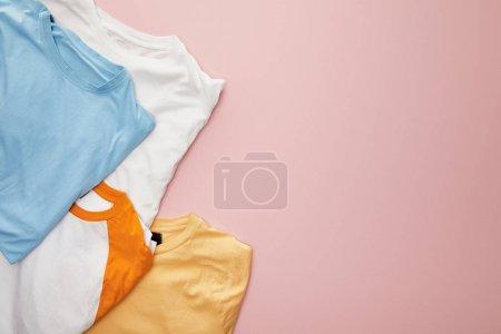 Photo pour Vue de dessus des t-shirts pliés blancs, jaunes, orange et bleus sur fond rose - image libre de droit