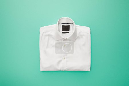 Photo pour Vue du dessus de la chemise pliée blanche unie sur fond turquoise - image libre de droit