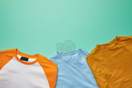 top view of folded orange, blue and ochre t-shirts on turquoise background