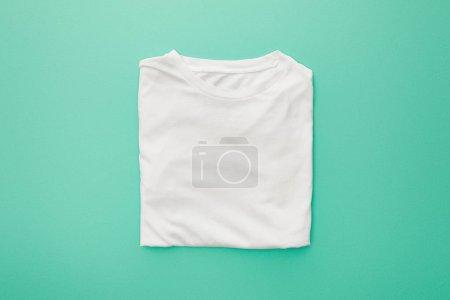 Photo pour Vue supérieure du t-shirt plié blanc blanc sur le fond turquoise - image libre de droit