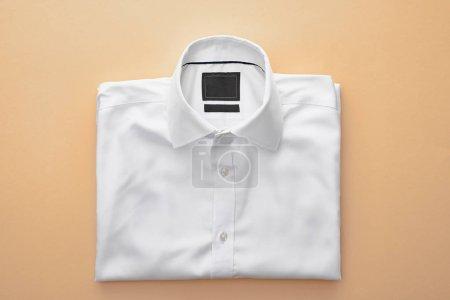 Photo pour Vue du dessus de la chemise pliée blanche unie sur fond beige - image libre de droit