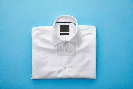 Photo pour Vue du dessus de la chemise pliée blanche unie sur fond bleu - image libre de droit