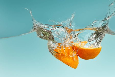 ripe orange halves falling in water with splashes on blue background