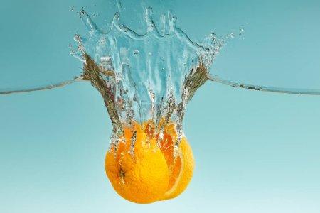 Photo pour Moitiés orange mûres tombant dans l'eau avec des éclaboussures sur le fond bleu - image libre de droit