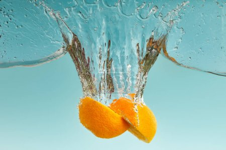 Photo for Tasty orange halves falling in water with splashes on blue background - Royalty Free Image