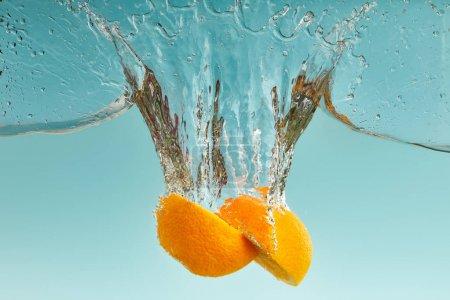 Photo pour Savoureux orange moitiés tombant dans l'eau avec éclaboussures sur fond bleu - image libre de droit