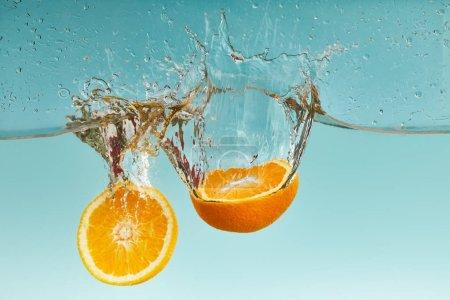 Foto de Mitades de color naranja brillante cayendo en el agua con salpicaduras sobre fondo azul - Imagen libre de derechos