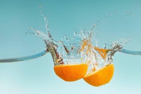 Photo pour Moitiés orange fraîches tombant dans l'eau avec des éclaboussures sur le fond bleu - image libre de droit