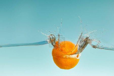 Photo pour Orange coupé tombant dans l'eau avec des éclaboussures sur le fond bleu - image libre de droit