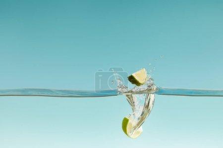 Photo pour Moitiés mûres de chaux tombant profondément dans l'eau avec des éclaboussures sur le fond bleu - image libre de droit