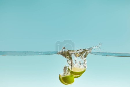 Photo for Lime halves falling deep in water with splash on blue background - Royalty Free Image
