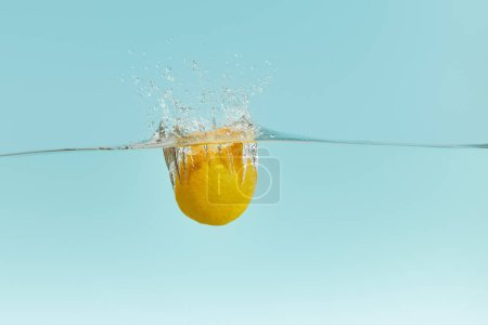Photo for Lemon falling deep in water with splash on blue background - Royalty Free Image