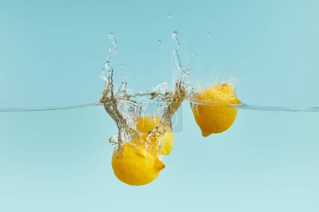 Photo for Lemons falling deep in water with splash on blue background - Royalty Free Image
