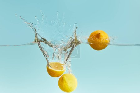 Photo for Fresh ripe lemons falling deep in water with splash on blue background - Royalty Free Image