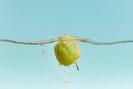Photo pour Pomme verte mûre dans l'eau avec des bulles sur le fond bleu - image libre de droit