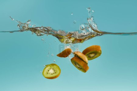Photo for Kiwi slices falling deep in water with splash on blue background - Royalty Free Image