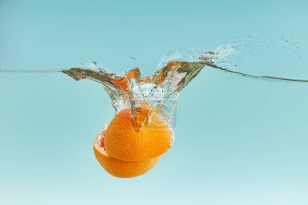 Photo for Fresh orange halves falling in water on blue background - Royalty Free Image