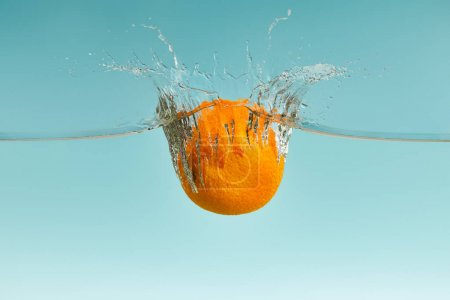 Photo for Fresh orange falling in water with splash on blue background - Royalty Free Image