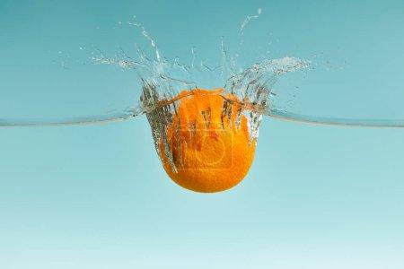 Photo pour Orange fraîche tombant dans l'eau avec éclaboussure sur fond bleu - image libre de droit