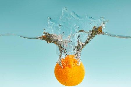 Photo pour Orange frais mûr tombant dans l'eau avec l'éclaboussure sur le fond bleu - image libre de droit