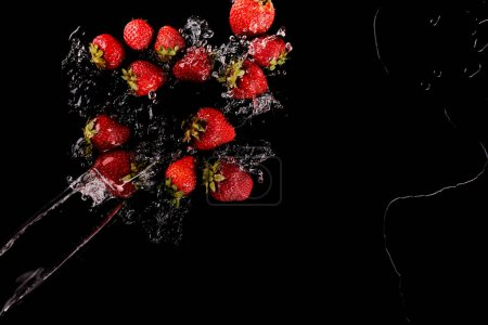 Photo for Top view of ripe red strawberries with clear water splash isolated on black - Royalty Free Image