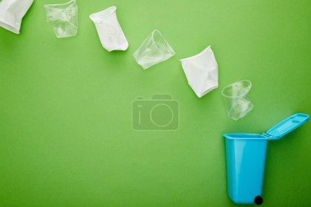 Foto de Vista superior de tazas de plástico arrugado cerca de la papelera de reciclaje azul en el fondo verde - Imagen libre de derechos