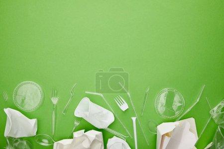 Photo pour Vue du haut des gobelets en plastique jetables, fourchettes, cuillères et récipients en carton sur fond vert avec l'espace de copie - image libre de droit