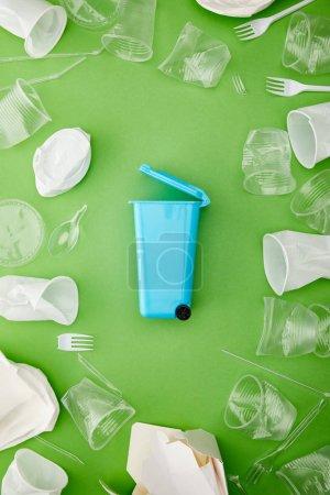 Photo pour Vue supérieure du bac bleu de recyclage entre les tasses en plastique froissées sur le fond vert - image libre de droit